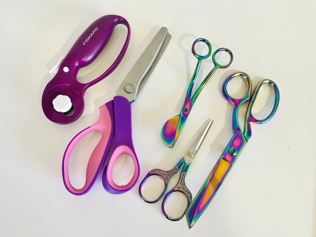 A purple rotary cutter, purple and pink pinking shears, oil slick rainbow duck bill scissors, oil slick thread snips, and oil slick fabric shears sit on a white backdrop