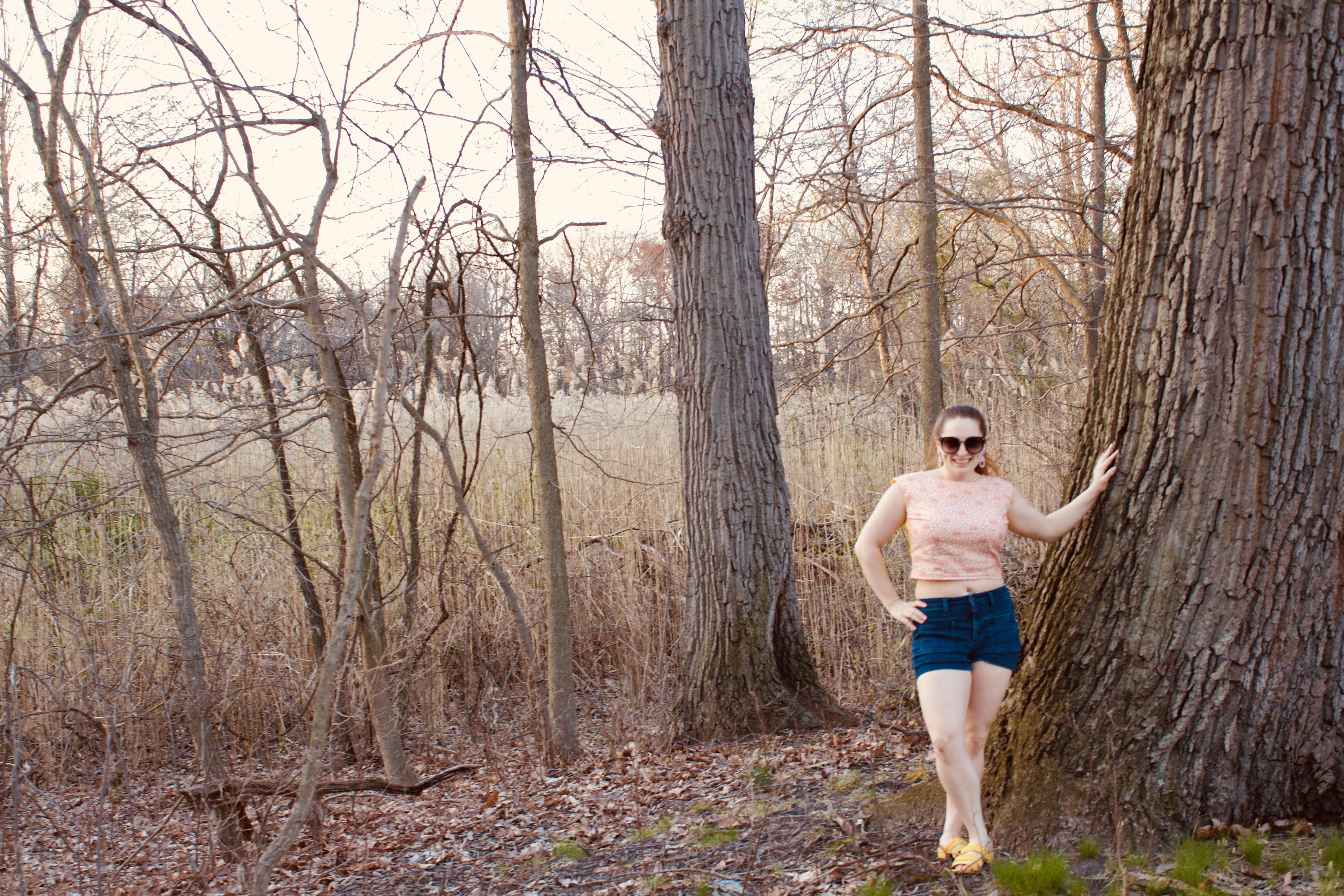 A person leans against a tree while wearing a pink crop top, and denim shorts.