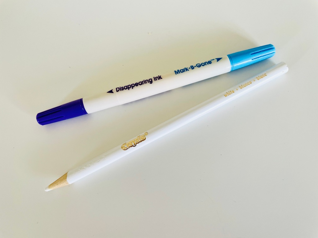 A double-sided Dritz Mark-be-Gone disappearing ink pen sits next to a Crayola white colored pencil on a white surface.