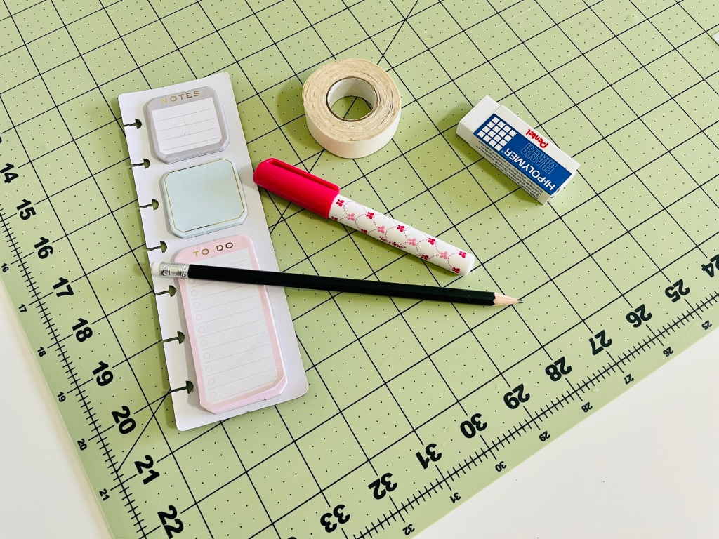 A pencil, sticky notes, fabric glue stick, fabric tape, and eraser sit on a green cutting mat