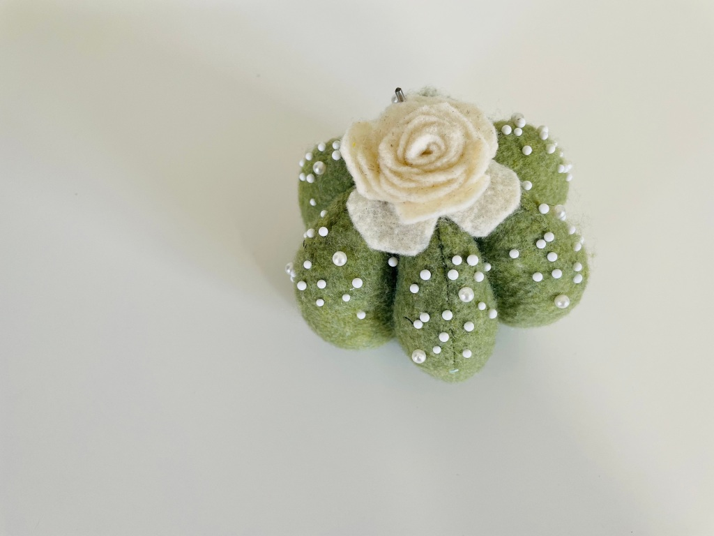 A succulent-shaped green pin cushion with a cream-colored flower and white pins throughout sits on a white background.