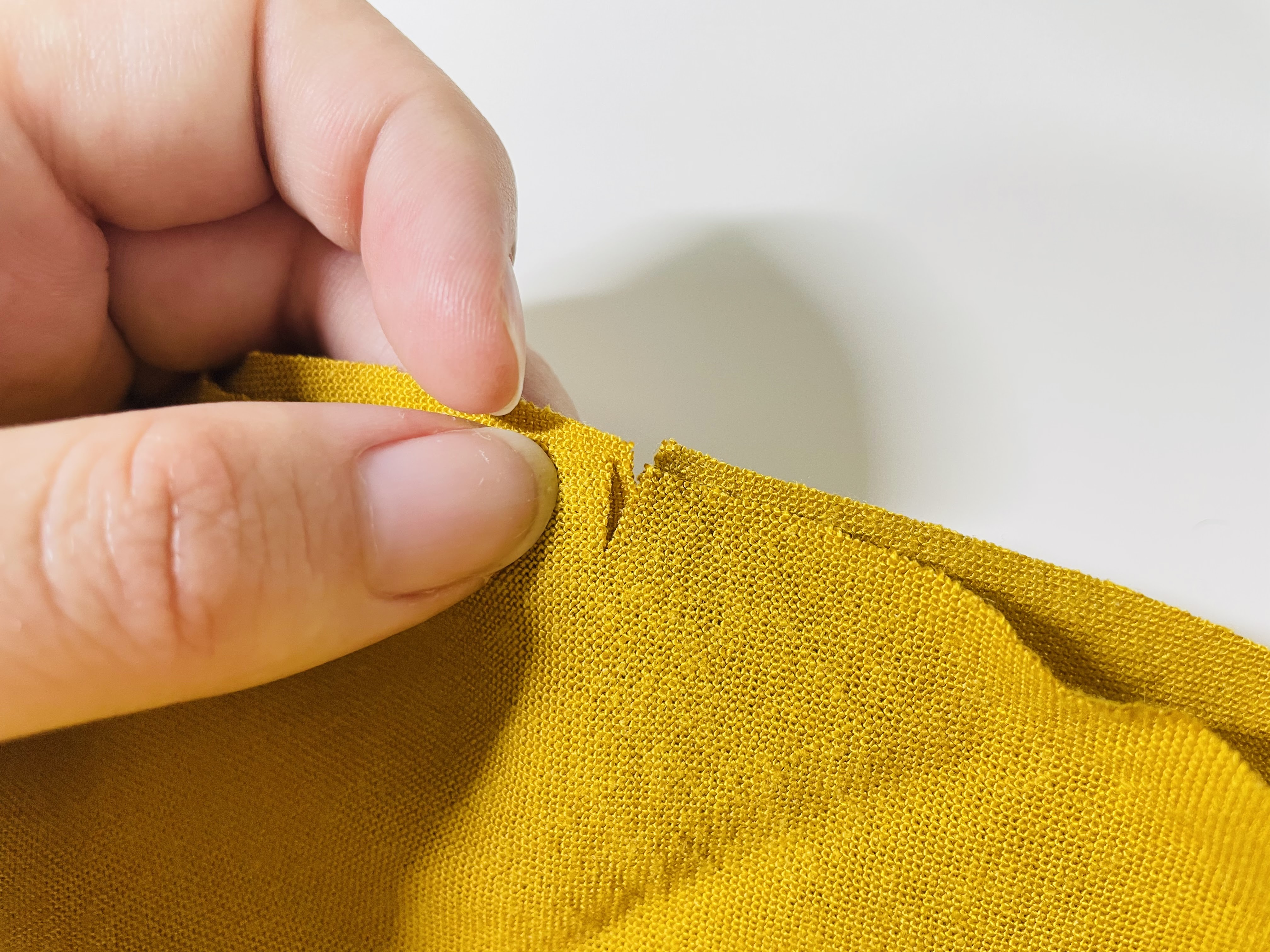 Lindsie holds two notched pieces of fabric together so that their notches align