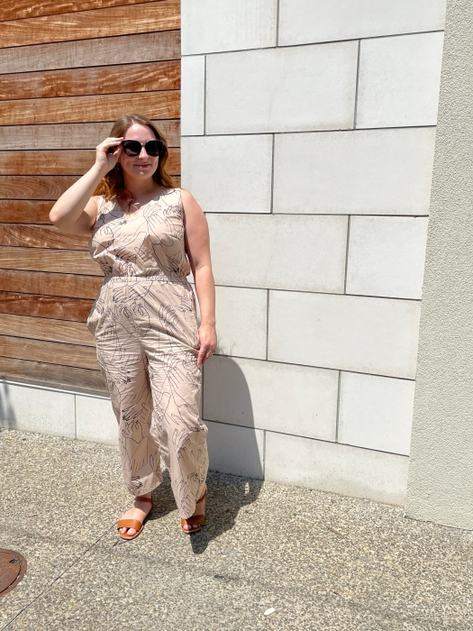 Lindsie, a white woman in her 20s, stands on a sidewalk in front of a wall that is partially wood and partially marble tiled and models a jumpsuit. The jumpsuit is sleeveless and 7/8 length and is made from a tan-colored material with black outlines of hands throughout. Lindsie has her hand on her sunglasses and looks in the distance. End.